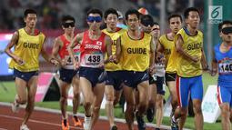Pelari 5000 meter putra kategori T11 Asian Para Games 2018 saat laga final di SUGBK, Jakarta, Jumat (12/10). Pemandu kategori T11 juga harus memiliki fisik dan kemampuan yang sama atau lebih dari pelari utamanya. (Liputan6.com/Helmi Fithriansyah)