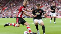 Striker Southampton, James Ward-Prowse, berebut bola dengan gelandang Manchester United, Daniel James, pada laga Premier League di Stadion St Mary's, Southampton, Sabtu (31/8). Kedua klub bermain imbang 1-1. (AP/Mark Kerton)