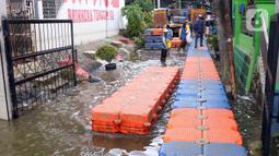 Petugas membuat jembatan apung saat banjir melanda Perumahan Periuk Damai, Tangerang, Banten, Selasa (23/2/2021). Adanya jembatan apung mempermudah warga saat melintasi banjir setinggi 2,5 meter di tempat tersebut. (Liputan6.com/Angga Yuniar)