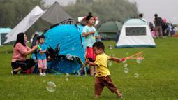 Seorang anak bermain gelembung saat orang-orang berkemah di gunung yang indah di Yanqing, Beijing pada 30 Agustus 2020. China memiliki lebih dari 200 orang yang dirawat di RS karena COVID-19, dengan lebih dari 300 lainnya diisolasi setelah dites positif terkena virus tanpa gejala. (AP/Andy Wong)