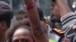 Pemuda Papua saat aksi di kawasan depan Istana Negara, Jakarta, Kamis (2/8). Aksi ini untuk memperingati 49 tahun penentuan pendapat rakyat (Pepera) 1969. (Liputan6.com/Helmi Fithriansyah)