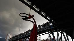 Sejumlah mahasiswa bergelantungan menggunakan tali pada sebuah jembatan saat menuntut peningkatan anggaran pendidikan di Bogota, Kolombia, Rabu (31/10). (AP Photo/Fernando Vergara)