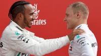 Juara F1 GP Jerman, pembalap Mercedes Lewis Hamilton bersama pembalap Ferrari dari Finlandia, Vatteri Bottas yang menempati posisi kedua merayakan kemenangan di ats podium Sirkuit Hockenheim, Minggu (22/7). (AP/Jens Meyer)
