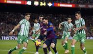 Aksi Lionel Messi yang berhadapan dengan lini pertahanan Real Betis pada laga lanjutan La Liga 2018/19 yang berlangsung di stadion Camp Nou. Barcelona kalah 3-4. (AFP/Josep Lago)
