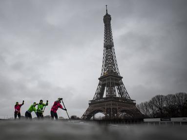 Para peserta Nautic Paddle Race atau lomba dayung sambil berdiri melintas dekat Menara Eiffel di Sungai Seine, Paris, Minggu (8/12/2019). Sekitar 1000 pesaing ikut serta dalam lomba sejauh 11 kilometer menyeberangi sungai Seine dengan pemandangan kota Paris. (Photo by Olivier MORIN / AFP)