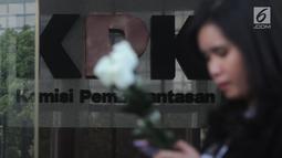 Seorang wanita membawa bunga mawar menyambut kedatangan penyidik senior KPK, Novel Baswedan saat masuk kerja kembali di gedung KPK, Jakarta, Jumat (27/7). Hingga sekarang penyiram air keras  Novel belum di tangkap. (Merdeka.com/Dwi Narwoko)