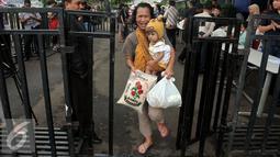 Warga membawa Paket  Sembako Murah oleh  PT Indosiar Visual Mandiri  di Studio 5 Indosiar, Jakarta, (10/6). Pembagian  Sembako Murah ini hanya di sekitaran wilayah kerja perusahaan PT Indosiar di Jalan Daan Mogot. (Liputan6.com/Johan Tallo)