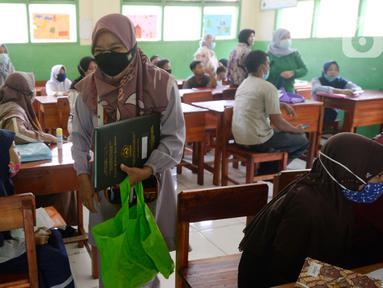 Wali murid siswa Sekolah SD kelas 4,5 dan 6 usai mengambil rapot secara bergilir di Sekolah Islam Raudlatul Hikmah, Parakan, Pondok Benda, Pamulang, Tangerang Selatan, Banten, Jumat (16/10/2020). (merdeka.com/Dwi Narwoko)