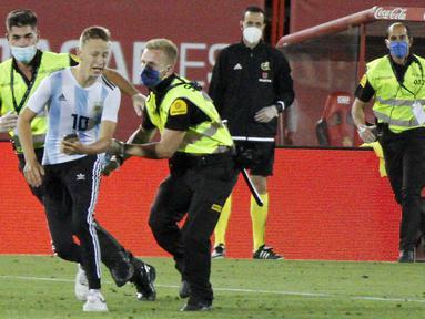 Petugas keamanan menangkap seorang penyusup yang masuk ke lapangan saat pertandingan La Liga antara Mallorca dengan FC Barcelona di Son Moix Stadium, Palma de Mallorca, Spanyol, Sabtu (13/6/2020). Dalam pertandingan tersebut Barcelona mengalahkan Mallorca dengan skor 4-0. (AP Photo/Francisco Ubilla)