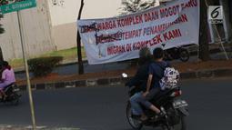 Pengendara motor melintasi spanduk penolakan lokasi penampungan pencari suaka di Kalideres, Jakarta, Selasa (16/7/2019). Sebelumnya, para pencari suaka dari berbagai negara berkonfilk ini tinggal di pinggir jalan dan trotoar di kawasan Kebon Sirih, Jakarta. (Liputan6.com/Helmi Fithriansyah)
