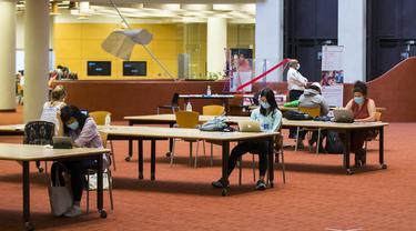 Orang-orang yang memakai masker menjaga jarak saat belajar di sebuah perpustakaan di Toronto, Kanada (24/8/2020). Tahap ketiga rencana pembukaan kembali Perpustakaan Umum Toronto dimulai pada Senin (24/8). (Xinhua/Zou Zheng)