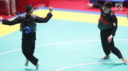 Pesilat Indonesia, Iqbal Candra Pratama saat bertarung melawan Pesilat Thailand, Porntep Poolkaew di Arena Pendopo Pencak Silat TMII, Jakarta, Kamis (23/8). Pesilat Iqbal unggul dengan skor 5-0 dan maju ke 8 besar. (Liputan6.com/Fery Pradolo)