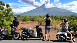 Sejumlah turis mengabadikan pemandangan erupsi Gunung Agung di Kabupaten Karangasem, Bali, Jumat (6/7). Mereka sibuk mengabadikan semburan abu vulkanik Gunung Agung.  (AFP FOTO / Sonny Tumbelaka)