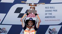 Pembalap Repsol Honda, Marc Marquez mengangkat trofi juara MotoGP Spanyol 2018 di Sirkuit Jerez, Minggu (6/5). Kemenangan ini jadi kedua beruntun bagi Marquez setelah dua pekan lalu juga jadi kampiun pada MotoGP AS. (AP Photo/Miguel Morenatti)