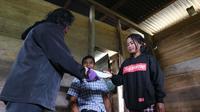 Seorang guru di SMPN 16 Sigi memberikan soal pelajaran ke siswanya di Dongi-dongi untuk dikerjakan, Rabu (22/7/2020). Cara itu jadi salah satu pola ajar yang diterapkan di wilayah terpencil di Kabupaten Sigi. (Foto:Liputan6.com/ Heri Susanto).