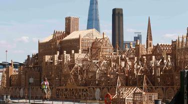 Seorang pekerja menyelesaikan pembuatan patung skyline Kota London sepanjang 120 meter di London, Inggris, (30/8). Patung ini akan dibakar dalam sebuah acara untuk mengenang bencana Kebakaran besar London pada 1666. (REUTERS/Peter Nicholls)
