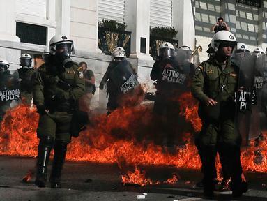 Sejumlah polisi anti huru-hara melawan aksi demonstran yang melemparkan bom api di Athena, Yunani, (12/11/2015). Para Demonstran memprotes langkah-langkah penghematan yang diminta oleh badan pinjaman internasional. (REUTERS/Alkis Konstantinidis)