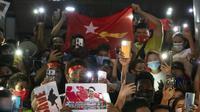 Warga Myanmar yang tinggal di Thailand memegang foto pemimpin Myanmar Aung San Suu Kyi dan menyalakan lampu ponsel saat protes di depan Kedutaan Besar Myanmar di Bangkok, Thailand, Kamis (4/2/2021). Warga memprotes kudeta militer yang terjadi Myanmar. (AP Photo/Sakchai Lalit)