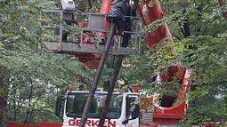 Polisi berusaha menangkap aktivis lingkungan di sebuah rumah pohon di hutan Hambacher Forst, Jerman Barat (13/9). Aktivis tersebut tinggal di rumah pohon untuk  melindungi hutan kuno dari razed untuk tambang batu bara di dekatnya. (Henning Kaiser/dpa/AFP)