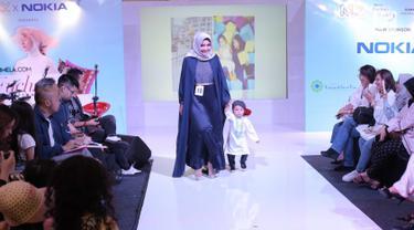 Seorang ibu bersama anaknya berjalan di atas catwalk dalam fashion show Fabalous Mom and Kids 2018 di Fimela Fuchsia Market 2018 di Kota Kasablanka, Jakarta (27/5). (Liputan6.com/Faizal Fanani)