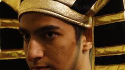 Suporter Mesir memakai hiasan kepala Firaun saat menyambut gelaran Piala Dunia di Jalan Nikolskava, Moskow, Rabu (13/6/2018). Piala Dunia 2018 akan berlangsung pada 14 Juni hingga 15 Juli mendatang. (AP/Rebecca Blackwell)