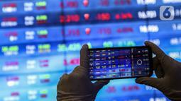 Karyawan mengambil gambar layar Indeks Harga Saham Gabungan (IHSG) di Bursa Efek Indonesia, Jakarta, Jumat (22/1/2021). Sebanyak 111 saham menguat, 372 tertekan, dan 124 lainnya flat. (Liputan6.com/Johan Tallo)