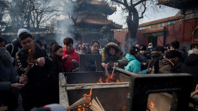 Sejumlah warga membakar dupa untuk berdoa keberuntungan pada hari kelima Tahun Baru Imlek di Yonghegong, atau Kuil Lama di Beijing (9/2). Warga China merayakan Tahun Babi tersebut dengan doa, pesta keluarga, dan belanja. (AFP Photo/Nicolas Asfouri)#source%3Dgooglier%2Ecom#https%3A%2F%2Fgooglier%2Ecom%2Fpage%2F%2F10000