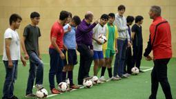 Para imigran mendapatkan instruksi dari pelatih sepak bola profesional yang berasal dari klub FK Austria Wien di Wina, Austria. (Reuters/Heinz-Peter Bader)