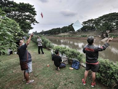 Warga bermain layang-layang di pinggir Kanal Banjir Timur (KBT), Duren Sawit, Jakarta, Senin (19/4/2021). KBT menjadi lokasi favorit warga untuk mengisi waktu menunggu buka puasa atau ngabuburit, salah satunya dengan bermain layang-layang bersama keluarga. (merdeka.com/Iqbal S Nugroho)