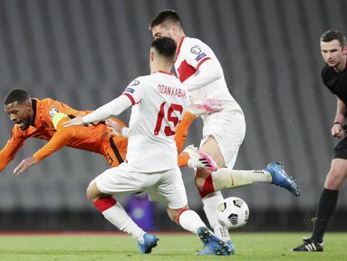 Gelandang Belanda, Georginio Wijnaldum, terjatuh saat berebut bola dengan bek Turki, Ozan kabak, pada laga kualifikasi Piala Dunia 2022 di Stadion Olimpiade Ataturk, Kamis (25/3/2021). Turki menang dengan skor 4-2. (Tolga Bozoglu/Pool Photo via AP)