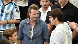Suami Victoria Beckham itu (tengah) tampil santai dengan mengenakan kaus putih berpadu kemeja denim di stadion Maracana, Brasil, Senin (14/7/14). (AFP PHOTO/Nelson Almeida)