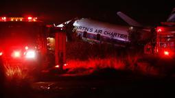 Sebuah pesawat terbelah menjadi beberapa bagian setelah jatuh di dekat kota Pretoria, Afrika Selatan, Selasa (7/10). Pesawat yang membawa 19 penumpang termasuk pilot tersebut jatuh menabrak sebuah bangunan pabrik kecil. (AP/Phil Magakoe)