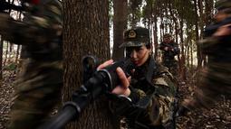 Tentara wanita China melakukan simualisi perang di tengah hutan saat melakukan latihan militer jelang Hari Perempuan Internasional di Hefei, China (6/4). (AFP)
