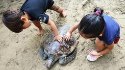 Dua anak memegang kura-kura hijau setelah dilepaskan di pantai Kuta di pulau Bali (27/3). Sekitar 18 kura-kura hijau diburu untuk diambil dagingnya dan dilepaskan kembali ke laut setelah polisi menangkap pelaku di Kabupaten Gianyar pada 13 Maret. (AFP Photo/Sonny Tumbelaka)
