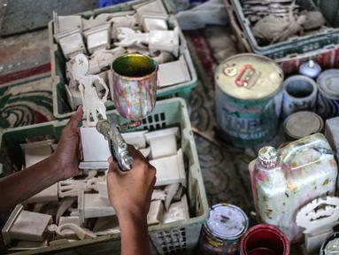 Pekerja mengecat plakat yang sedang dibuat di Industri Rumahan Pluit, Penjaringan, Jakarta Utara, Rabu (30/10/2019). Plakat yang terbuat dari bahan baku resin plastik tersebut dijual dengan harga Rp 50.000 hingga Rp 100.000. (Liputan6.com/Faizal Fanani)