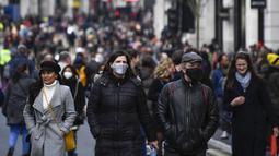 Orang-orang berjalan dengan mengenakan masker dan membawa tas belanjaan di Regent Street, setelah pelonggaran pembatasan virus corona COVID-19 menyusul berakhirnya kebijakan penguncian nasional atau lockdown kedua di Inggris, di London, Sabtu (5/12/2020). (AP Photo/Alberto Pezzali)