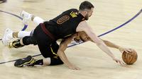 Pemain Warriors, Stephen Curry (bawah) berebut bola dengan pemain Cavaliers, Kevin Love pada gim pertama final NBA basketball di Oakland, California, (31/5/2018). Warriors menang 124-114. (AP/Marcio Jose Sanchez)