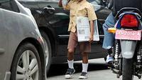 Seorang anak menjajakan koran di Jalan Tol Reformasi, Makassar (23/7). Data LPA Sulsel, sekitar 700 anak di Kota Makassar bekerja di sejumlah tempat dan sebagian besar menjadi pengemis. (Antara)