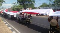 Komunitas vespa di Makassar mengarak bendera merah putih sepanjang 73 meter berkeliling kota Makassar dalam rangka memeriahkan perayaan HUT RI ke-73
