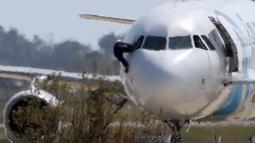 Salah seorang sandera diduga kru pesawat nekat keluar dari jendela kokpit, Siprus, Selasa (29/3). Pelaku yang diketahui bernama Seif Eldin Mustafa (27) menyerahkan diri dan membebaskan 5 sandera. (Reuters/Yiannis Kourtoglou)