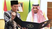 Presiden RI, Joko Widodo (Jokowi) memperlihatkan album foto dari pertemuan mereka di Bogor sehari sebelumnya untuk Raja Arab Saudi Salman bin Abdul Aziz di Jakarta, Kamis (2/3). (AFP PHOTO / PRESIDEN PALACE / Laily Rachev)