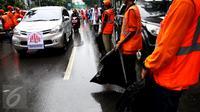 Kendaraan peserta aksi damai 2 Desember melewati pasukan oranye (petugas kebersihan) yang disiagakan di kawasan Monas, Jakarta, Jumat (2/12). Pasukan oranye dibekali kantong plastik besar untuk memungut sampah yang berserakan. (Liputan6.com/Johan Tallo)
