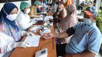 Petugas kesehatan memeriksa kesehatan warga Kelurahan Gedong untuk penyuntikkan vaksin COVID-19 di Jakarta, Rabu (23/6/2021). Vaksin bisa mengurangi tingkat keparahan infeksi dan kematian akibat virus, termasuk yang disebabkan varian Delta. (merdeka.com/Imam Buhori)