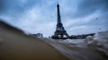 Menara Eiffel terlihat saat sungai Seine di Paris meluap, Prancis (7/1). Sungai Seine tidak mampu menampung debit air setelah hujan terjadi terus-menerus sehingga meluap sejajar dengan tinggi jalan. (AFP Photo/Olivier Morin)