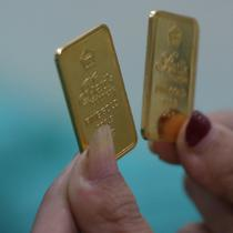 Petugas menunjukkan sampel logam mulia di Butik Emas Antam, Jakarta, Kamis, (23/7/2020). Usai cetak rekor ke posisi termahalnya di Rp 982 ribu, harga emas PT Aneka Tambang Tbk (Emas Antam) kembali turun Rp 5.000 menjadi Rp 977 ribu per gram pada perdagangan hari ini. (Liputan6.com/Angga Yuniar)