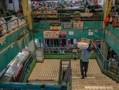Seorang pria memanggul barang di Pasar Pondok Labu, Jakarta, Rabu (10/2/2021). Satu pedagang dinyatakan positif Covid-19, meski begitu pengelola Pasar Pondok Labu tetap melanjutkan operasional pasar sambil melakukan penyemprotan cairan disinfektan selama tiga hari. (Liputan6.com/Faizal Fanani)
