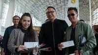 Peringati Hari Pelanggan Nasional, Garuda Indonesia, membagikan souvenir kepada penumpang GA 830 rute Jakarta – Singapura di Terminal 3 Bandara Internasional Soekarno Hatta.