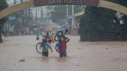 Sejumlah warga berjalan menembus genangan banjir yang diakibatkan oleh Topan Vamco di Provinsi Rizal, Filipina (12/11/2020). Topan Vamco membawa angin kencang dan hujan deras yang memicu tanah longsor, longsor batu, serta banjir bandang. (Xinhua/Rouelle Umali)