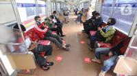 Penumpang menerapkan jaga jarak aman saat duduk dalam gerbong KRL tujuan Jakarta di Stasiun Bogor, Jawa Barat, Kamis (11/6/2020). PT KCI membatasi jumlah penumpang 35- 40 persen dari kapasitas untuk jaga jarak aman antarpengguna KRL atau sekitar 74 penumpang per gerbong. (merdeka.com/Arie Basuki)