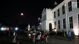 Warga menyaksikan gerhana bulan total di Kota Tua Jakarta, Rabu (31/1). Kegiatan tersebut dilakukan di halaman Museum Fatahillah. (Liputan6.com/Arya Manggala)
